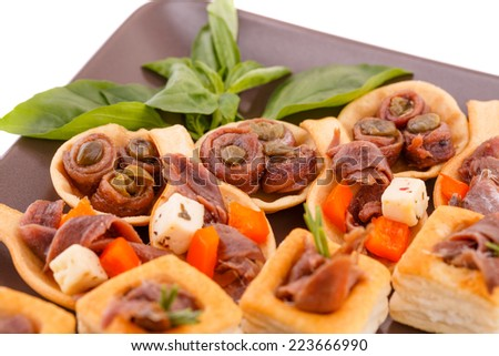 Anchovies in pastries, basil on brown plate. - stock photo