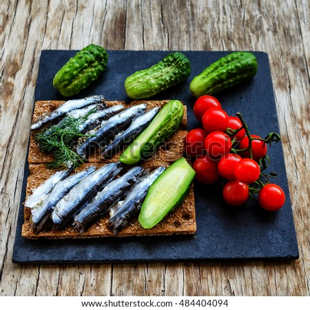 Anchovy with fresh cucumbers and cherry tomatoes on the black rectangular plate on the vintage wooden table, traditionally accompanied with vodka