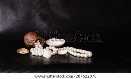 Ancient amphora, tropical sea shell and pearls over black - stock photo