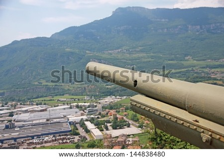 ancient and historic World War I gun with the barrel pointed toward the city - stock photo