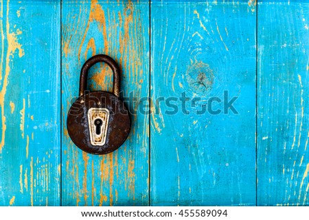 Ancient and rusty closed  padlock on old wooden table covered with blue paint. View from above