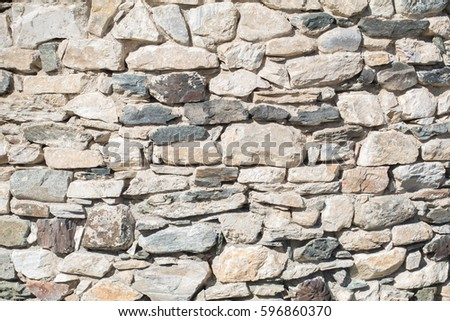 Ancient antique stone wall of medieval monastery or fortress. vintage background texture of masonry stone cement with cracks. Building facade.