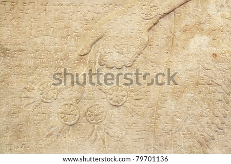 Ancient Assyrian wall carving of a hand with cuneiform writing - stock photo
