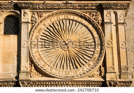 Ancient astronomical clock in Sun shape on the facade of famous Chartres cathedral (France). - stock photo
