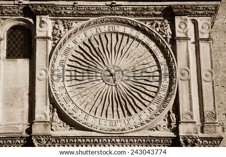 Ancient astronomical clock in Sun shape on the facade of famous Chartres cathedral (France). Aged photo. Sepia. - stock photo