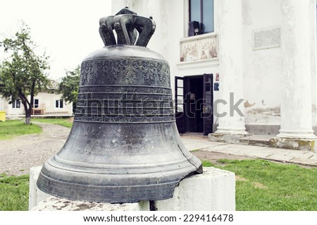 ancient bell put on pedestal in front of the church of Cuza castle, Ruginoasa, Romania