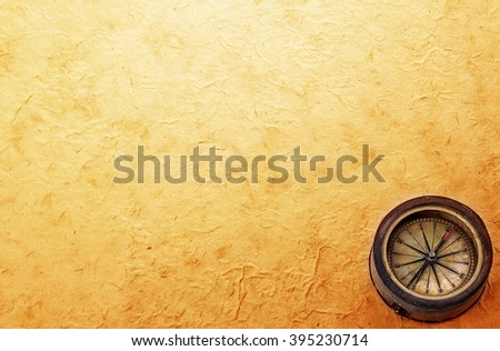 Ancient brass compass on vintage old paper background. Retro stale. - stock photo