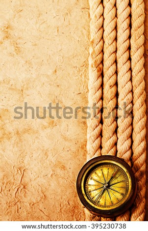 Ancient brass compass with rope on vintage old paper background. Retro stale. - stock photo