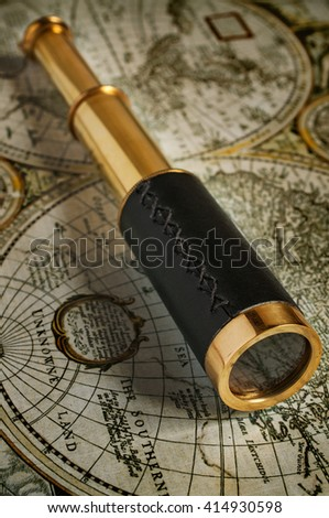Ancient brass telescope and old map close-up