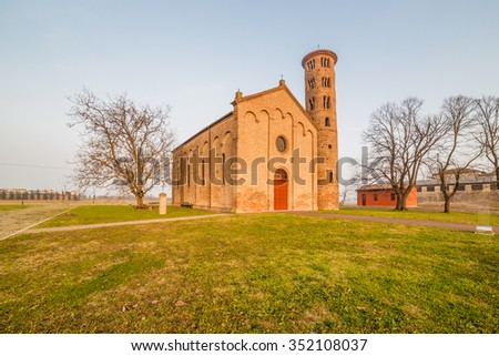 Ancient brick walls of an old Catholic church with one of the oldest  belltowers in Italy