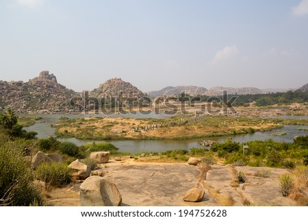 Ancient Bridge in Hampi. Currently only the pillars meant to support the top slabs of the bridge remain. The bridge is constructed at a point where the river makes a bifurcation and the island.