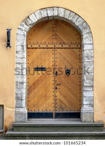 Ancient brown door texture with iron rivets and metal handle - stock photo