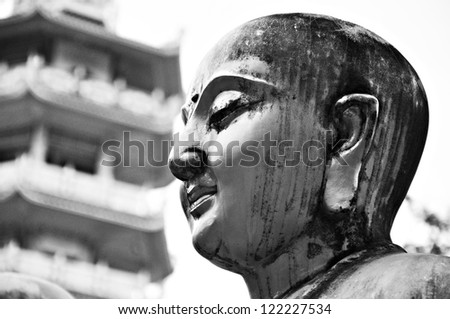 Ancient Buddha face statue in Chinese temple - stock photo
