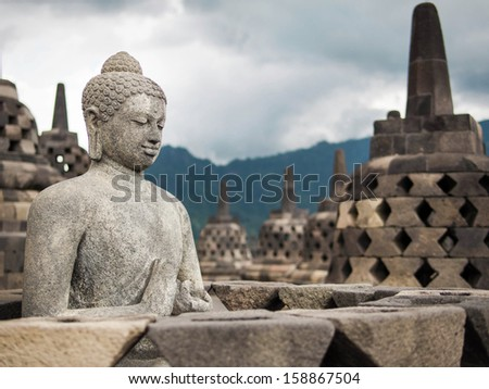 Ancient Buddha statue at Borobudur temple in Yogyakarta, Java, Indonesia. - stock photo