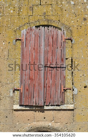 Ancient building window closed with wooden shutters.