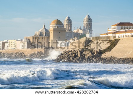 Ancient Cadiz Cathedral. The waves on the winter Atlantic Ocean. Spain - stock photo