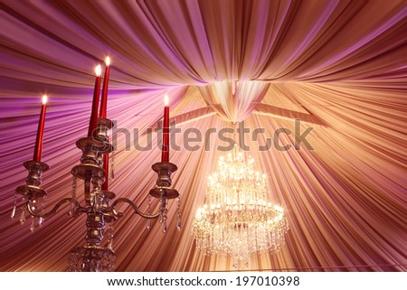 Ancient candle sticks and a chandelier on a wedding day - stock photo