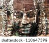 ancient carved face in angkor wat - stock photo