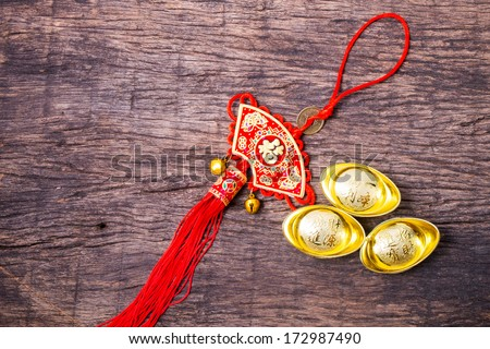 Ancient Chinese gold ingots and red Chinese tassel on wooden table for Chinese new year decoration - stock photo