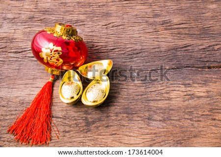 Ancient Chinese golden ingots and Chinese lantern on wooden table - stock photo