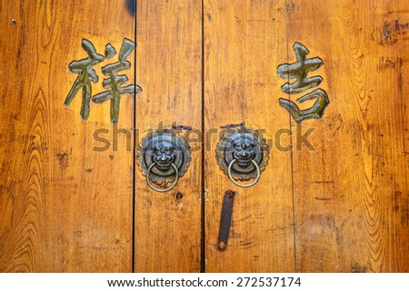 Ancient Chinese knocker. Text on the door translate into English is auspicious. Located in Old Town of Lijiang, Yunnan province, China. - stock photo