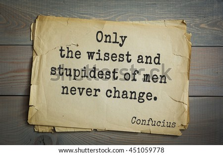 Ancient chinese philosopher Confucius quote on old paper background. Only the wisest and stupidest of men never change. - stock photo