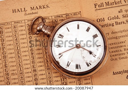 Ancient circa 1795 pocket watch on antique hall mark guide. - stock photo