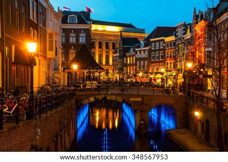 Ancient city center of Utrecht, Netherlands features many buildings from the Early Middle Ages. Illuminated Oudegracht area - a canal following the Rhine river - cafes, restaurants and shops