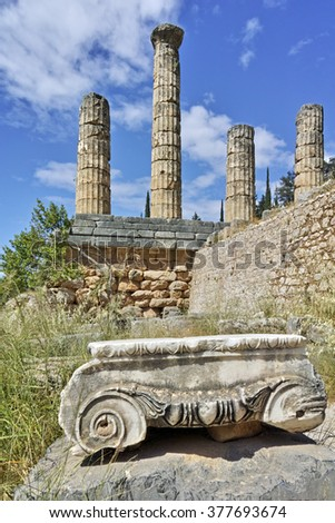 Ancient column and The Temple of Apollo in Ancient Greek archaeological site of Delphi,Central Greece - stock photo