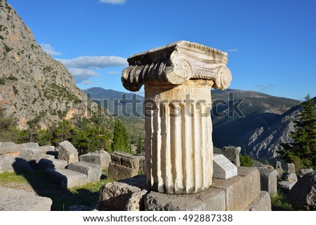 Ancient column in Ancient Greek archaeological site of Delphi shown at warm evening light, Central Greece