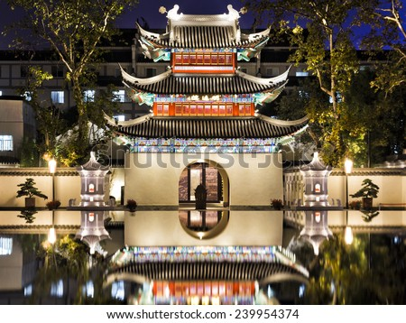 Ancient confucius temple in Chinese city Nanjing illuminated at sunset with still reflection of facade in waterpool - stock photo