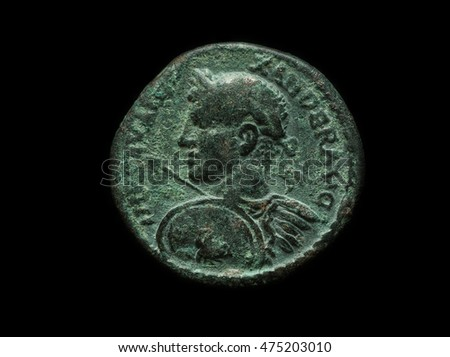 Ancient copper roman provincial coin with emperor portrait, close-up shot, isolated on black