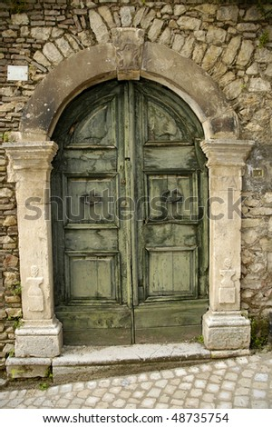 Ancient door on a stone wall - stock photo