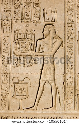 Ancient Egyptian bas relief carving of a priest making an offering to the god Ka.  Ka is a  figure in the belief of life after death. Dendera Temple, Qena, Egypt. Ancient temple, over 1000 years old. - stock photo