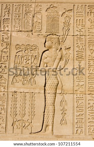 Ancient Egyptian bas relief of a priestess offering to the god of the Nile Hapi, also known as Hapy.  Carving on an outer wall of Dendera Temple, Qena, Egypt. Ancient carving, on display 1000 years. - stock photo