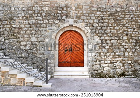 Ancient entrance to the historical building of the citadel in the old town of Budva, Montenegro. Heavy brown wooden door with black metal bar, old rough stone wall and marbel stairs in front - stock photo