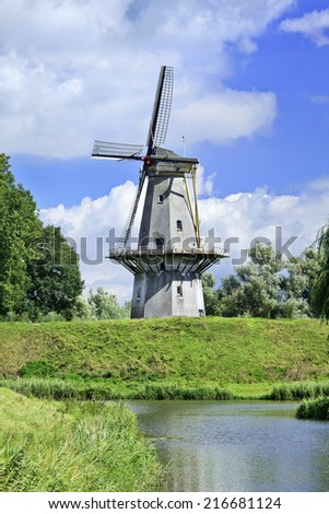Ancient floor mill build on a green city wall with a blue sky and dramatic clouds.  - stock photo