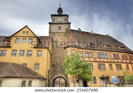 Ancient gate with clock tower and attached historical buildings in Rothenburg ob der Tauber, Germany - stock photo