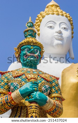Ancient Giant statue with blur Buddha imaged stutue background - stock photo