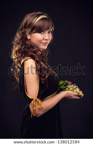 Ancient goddess stretch a bunch of grapes - stock photo