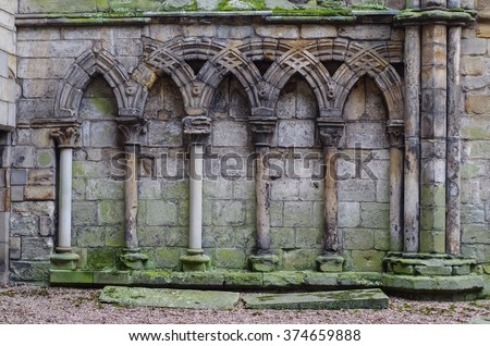 Ancient gothic stone wall with arches and columns, ruins Holyrood Palace in Edinburgh, Scotland, UK - stock photo