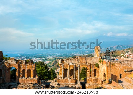 Ancient greek amphitheatre in Taormina city and mountain Etna in the back, Sicily island, Italy