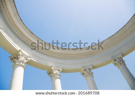 Ancient Greek columns against a blue sky and sea - stock photo