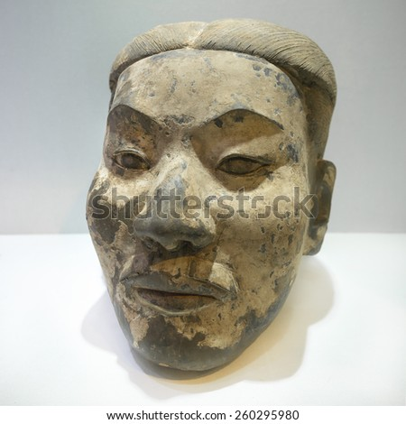 Ancient head of terracotta warrior for protection in afterlife. - stock photo