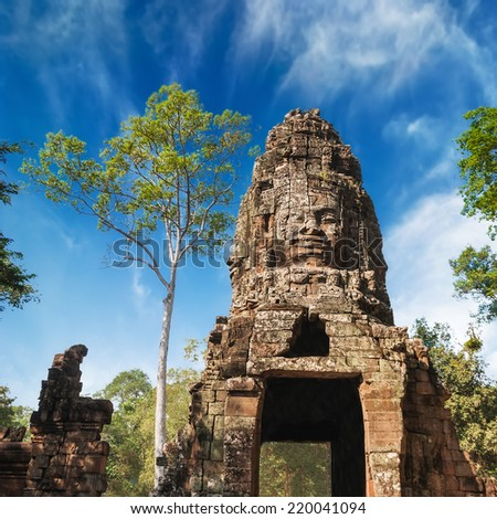 Ancient Khmer architecture. Buddha face at Ta Prohm temple entrance gate. Angkor Wat complex, Siem Reap, Cambodia travel destinations  - stock photo