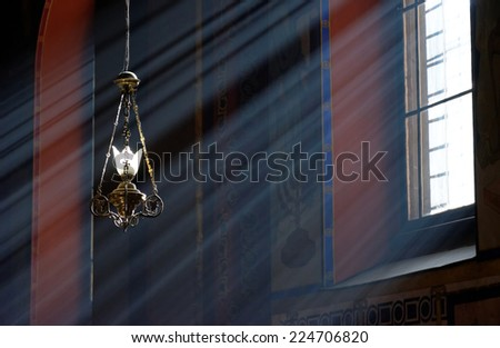 Ancient lantern in Armenian church of Lviv with sunbeams passing through the window - stock photo