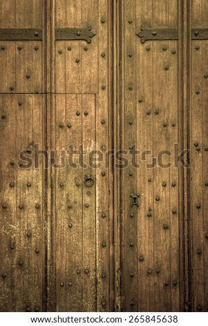 Ancient large wooden door with metal hinges and handle - stock photo