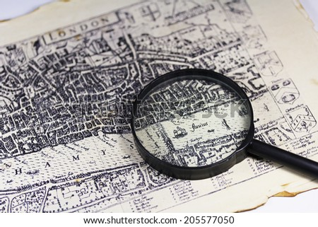 Ancient London map with a magnifier close up - stock photo
