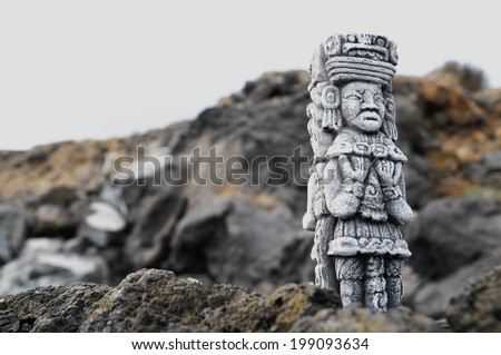 Ancient Maya Statue on the Rocks near the Ocean - stock photo