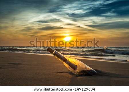 Ancient message in a bottle on a sea shore - stock photo